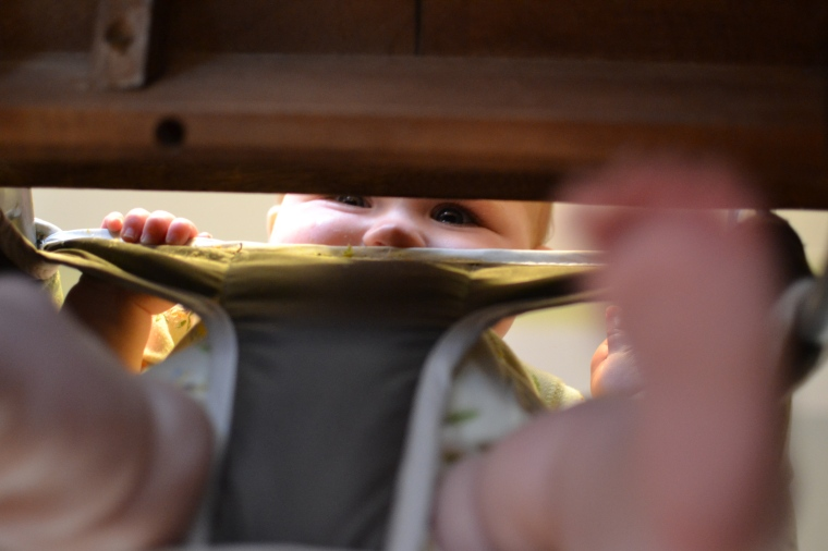 Peek-a-boo!  I see you!  Looking through the bottom of the high chair.
